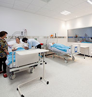 Tutor with sim patient and medical student in simulated ward