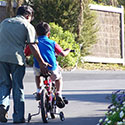 Father with boy on bike with training wheels